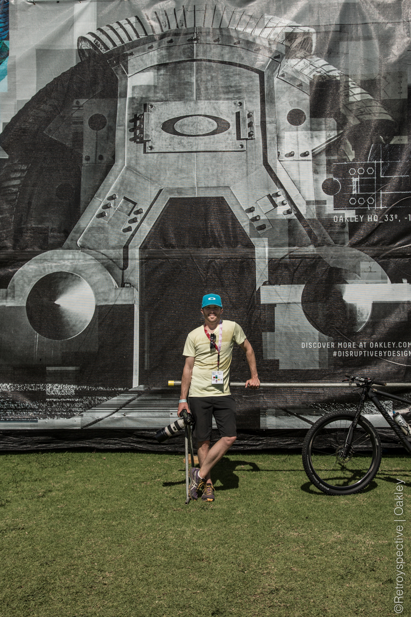 ©RETROYSPECTIVE-6353 John Ohail infront of an image of Oakley HQ